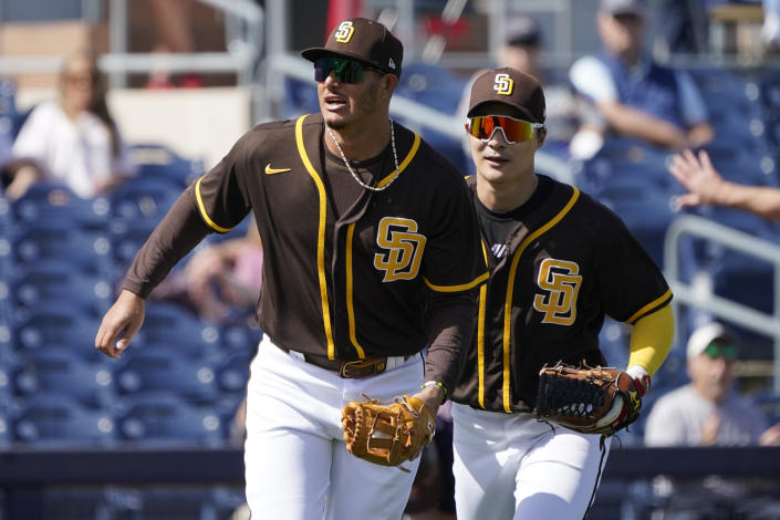 San Diego Padres' Manny Machado, left, runs off the field after tagging out Cleveland Indians' Bobby Bradley in the third inning a spring training baseball game Thursday, March 11, 2021, in Peoria, Ariz. (AP Photo/Sue Ogrocki)