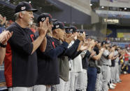 Cleveland Indians players and coaches applaud as pitcher Carlos Carrasco warms up during the seventh inning of a baseball game against the Tampa Bay Rays, Sunday, Sept. 1, 2019, in St. Petersburg, Fla. Carrasco is making his first appearance since May, after being diagnosed with leukemia. (AP Photo/Chris O'Meara)