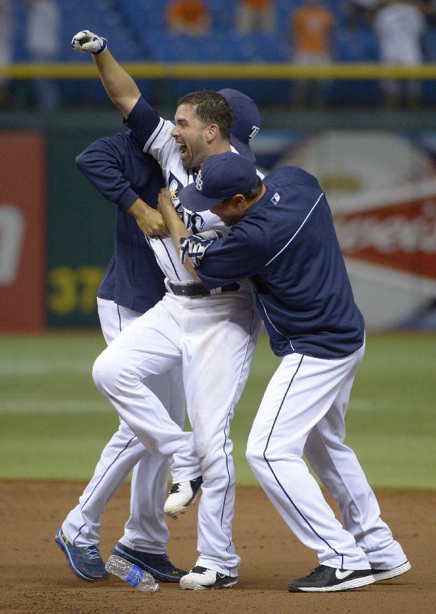 Tampa Bay Rays' David DeJesus, center, celebrates with teammates after hitting the game-winning single for a 5-4 win over the Baltimore Orioles in the 18th inning of the baseball game in St. Petersburg, Fla., Saturday, Sept. 21, 2013.(AP Photo/Phelan M. Ebenhack)