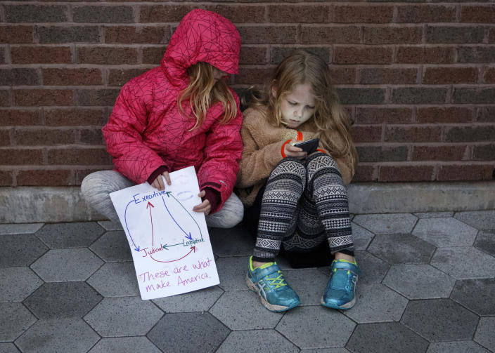 "<p>Seven-year-old Audrey Lucas, left, holds a sign showing the branches of the government as she looks at the phone her 9-year-old sister Addie is holding during a MoveOn ""Nobody Is Above the Law"" protest at Miller Park on Thursday, Nov. 8, 2018 in Chattanooga, Tenn. The protestors gathered to voice objections to President Trump's appointment of Matt Whitaker as acting attorney general. (Photo: C.B. Schmelter/Chattanooga Times Free Press via AP) </p>"