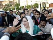FILE - In this Oct. 18, 2007 file photo, former Pakistan Prime Minister Benazir Bhutto, center, is surrounded by her supporters as she leaves her house for the airport, in Dubai, United Arab Emirates. Afghan President Ashraf Ghani, driven out by the Taliban, is the latest leader on the run to turn up in the United Arab Emirates. Others who found refuge in the Gulf Arab state include Bhutto, Spain's disgraced King Juan Carlos and former Thai prime ministers. (AP Photo/Kamran Jebreili, File)