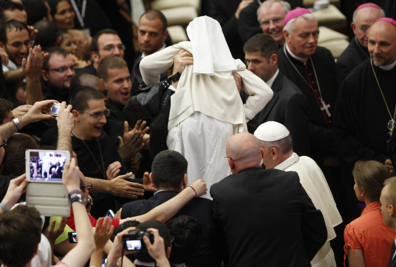 """A Vatican security officer holds up a nun as Pope Francis he arrives for a meeting with novices at the Paul VI hall, Vatican, Saturday, July 6, 2013. Pope Francis says the Catholic church needs to renew structures to accord with """"the places, the times."""" Francis has been waging a campaign to root out corruption and power plays in the Vatican's bureaucracy and to keep sight of what is essential in the church he was elected in March to lead. The Argentine-born pontiff offered the encouragement for renewal in a homily during Mass Saturday at the Vatican City hotel where he lives. Francis told Catholics """"not to be afraid of renewing some structures"""" to accord with """"the places, the times"""" and the people, but he didn't specify what needed to be changed. (AP Photo/Riccardo De Luca)"""