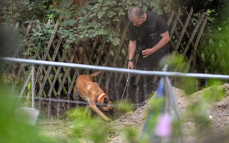 Police with sniffer dogs searched the allotment earlier this week - Martin Meissner/AP