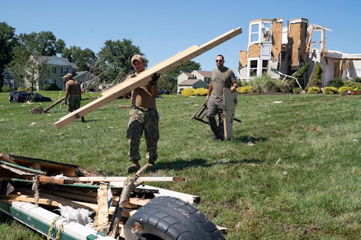A group of Navy recruiters help clear debris from a house destroyed by a tornado in Mullica Hill, New Jersey after flash floods caused by Ida killed at least 14 people.