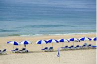 <p>Lounge chairs and umbrellas line a beach in Montauk, known for its white sand and 70-foot-high bluffs.</p>