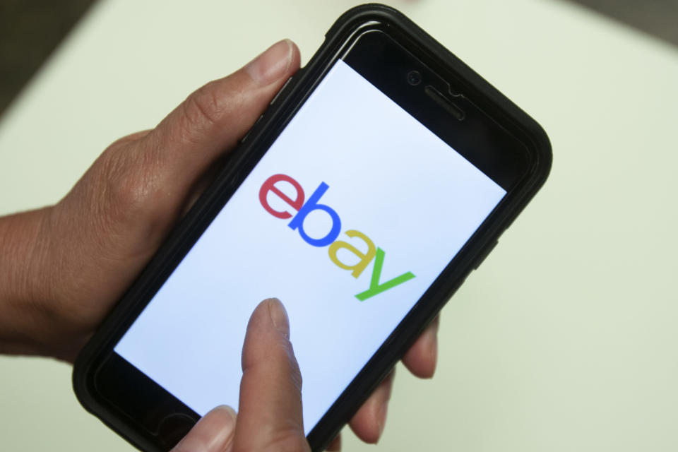 """FILE - In this July 11, 2019 file photo, an eBay app is shown on a mobile phone in Miami. A Massachusetts couple subjected to threats and other bizarre harassment from former eBay Inc. employees filed a civil lawsuit against the Silicon Valley giant on Wednesday, July 21, 2021. David and Ina Steiner say in their lawsuit filed in Boston federal court that the company engaged in a conspiracy to """"intimidate, threaten to kill, torture, terrorize, stalk and silence them"""" in order to """"stifle their reporting on eBay."""". (AP Photo/Wilfredo Lee, File)"""