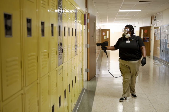 GermBlast employee Jade Davis fumigates disinfectant onto student lockers at Bowie Middle School in Odessa, Texas on Tuesday, July 28, 2020. The cleaning crew that Davis is part of is one of many measures to be implemented to help ensure the safety of students and school staff from COVID-19 in the case of an in-person return to school in Odessa. (Eli Hartman/Odessa American via AP)