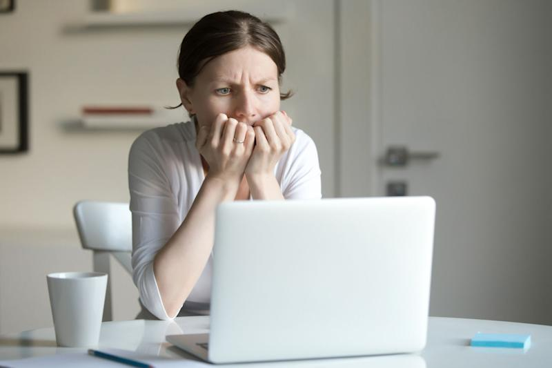 Woman worriedly looking at a laptop screen.