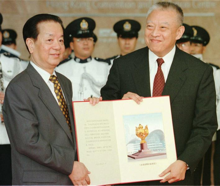 """FILE - In this file photo taken Tuesday, July 1, 1997, then Hong Kong's newly inaugurated Chief Executive Tung Chee-hwa, right, receives a book bearing a picture of a statue from then Chinese Foreign Minister Qian Qichen during a ceremony in Hong Kong. On July 1, 1997, Tung Chee-Hwa, the first chief executive of Hong Kong, declared: """"For the first time in history, we, the people of Hong Kong, will be master of our own destiny."""" (Pool Photo via AP Photo, File)"""