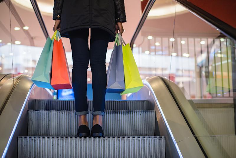 Woman going up escalator holding two shopping bags in each hand.