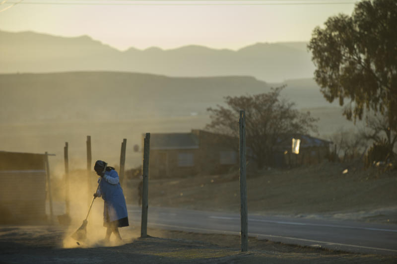 A woman sweeps in front of her house in a village near Maseru on September 2, 2014 (AFP Photo/Mujahid Safodien)