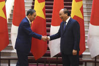 Japan's Prime Minister Yoshihide Suga, left, shakes hands with Vietnam's Prime Minister Nguyen Xuan Phuc after the exchange of documents at the Government Office in Hanoi Monday, Oct. 19, 2020. (Nhac Nguyen/Pool Photo via AP)