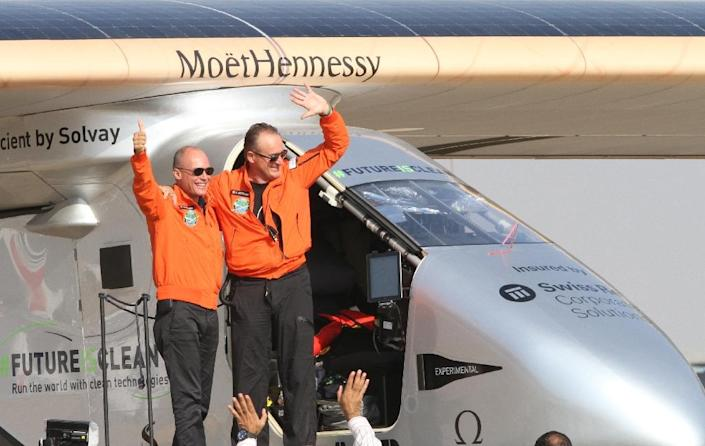 Swiss pilots Bertrand Piccard (left) and Andre Borschberg wave to supporters after the Solar Impulse 2 landed at Cairo International Airport on July 13, 2016 (AFP Photo/)