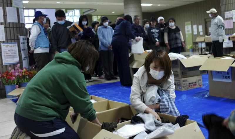 Evacuees choose clothes distributed at an evacuation center in Fukushima City, Fukushima Prefecture, northeastern Japan, Friday, April 22, 2011. (AP Photo/Sergey Ponomarev)