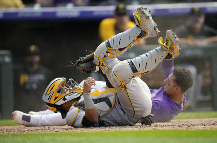 Pittsburgh Pirates catcher Michael Perez, front, tumbles after tagging out Colorado Rockies' Dom Nunez as he tries to score on a single by pinch-hitter Yonathyan Daza in the seventh inning of a baseball game Wednesday, June 30, 2021, in Denver. (AP Photo/David Zalubowski)