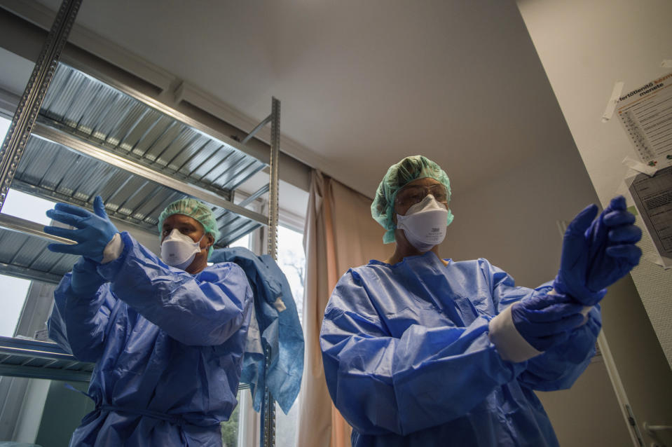Doctors take on protective suits before they enter the isolation room at the care unit of the new COVID-19infected patients inside the Koranyi National Institute of Pulmonology in Budapest, Hungary, Wednesday, March 25, 2020. (Zoltan Balogh/MTI via AP)