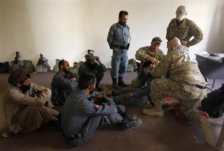 U.S. military advisors for NATO Training Mission-Afghanistan (NTM-A) conduct Combat First Aid lessons with Afghan policemen inside a police station in Khas Konar district in Kunar