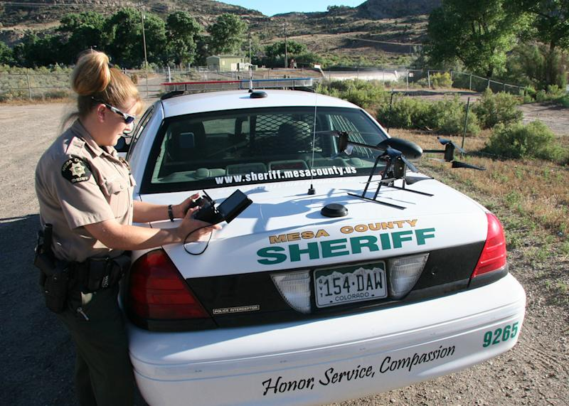 This undated photo provided by the Mesa County, Colo., Sheriff's Department, Deputy Amanda Hill of the Mesa County Sheriff's Office in Colorado prepares to use a Draganflyer X6 drone equipped with a video camera to help search for a suspect in a knife attack in Mesa County, Colo. Civilian cousins of the unmanned military aircraft that have been tracking and killing terrorists in the Middle East and Asia are being sought by police departments, border patrols, power companies, news organizations and others who want a bird's-eye view. (AP Photo/Mesa County Sheriff's Unmanned Operations Team)