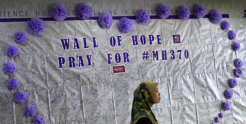 FILE - In this March 23, 2014 photo, a woman walks past a message board for passengers aboard a missing Malaysia Airlines plane, at a shopping mall in Kuala Lumpur, Malaysia.   With no answers yet in the disappearance of Malaysia Airlines Flight 370, investigators have said they're considering many options: hijacking, sabotage, terrorism or catastrophic equipment failure. Nobody knows if the pilots are heroes who tried to save a crippled airliner or if one collaborated with hijackers or was on a suicide mission. The mystery has raised concerns about whether airlines and governments do enough to make sure that pilots are mentally fit to fly.  (AP Photo/Lai Seng Sin)