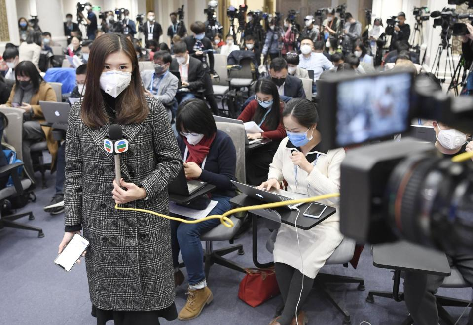 Journalists wear masks at a press room in Beijing on Sunday. Source: AAP