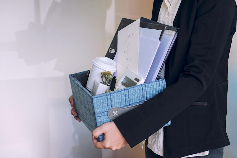 business woman carrying packing up all his personal belongings and files into a brown cardboard box to resignation in modern office, resign concept. (business woman carrying packing up all his personal belongings and files into a brown cardboard box t