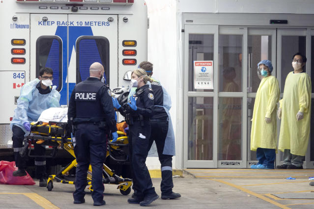 Hospital staff dressed in protective equipment stand by as a patient is taken out of an ambulance at Toronto's Mount Sinai Hospital, Sunday, March 29, 2020. The new coronavirus causes mild or moderate symptoms for most people, but for some, especially older adults and people with existing health problems, it can cause more severe illness or death. (Chris Young/The Canadian Press via AP)