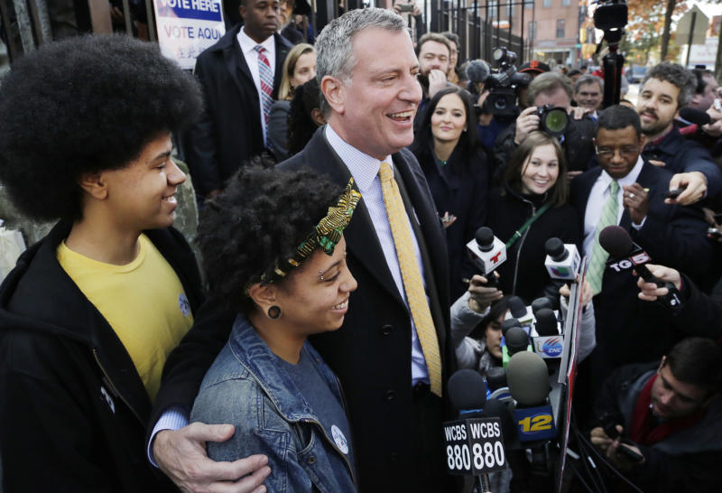 Democratic mayoral candidate Bill de Blasio embraces his daughter Chiara as he talks to the media after voting, Tuesday, Nov. 5, 2013 in the Park Slope neighborhood of the Brooklyn borough of New York. His son Dante is at left. De Blasio is running against Republican candidate Joseph Lhota. (AP Photo/Mark Lennihan)