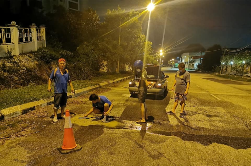 Rather than whine about the inaction of authorities, a group of Bercham residents in Ipoh has taken upon themselves to refill potholes in the area. — Courtesy photo from Phuah Tuck Jun