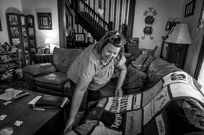 <p>Beth Genslinger mourns the death of her son Andy, who died from a heroin overdose in his bedroom in Germantown Ohio. This blanket features favorite T-Shirts and sports uniforms, stitched together in memorial. (Photograph by Mary F. Calvert for Yahoo News) </p>