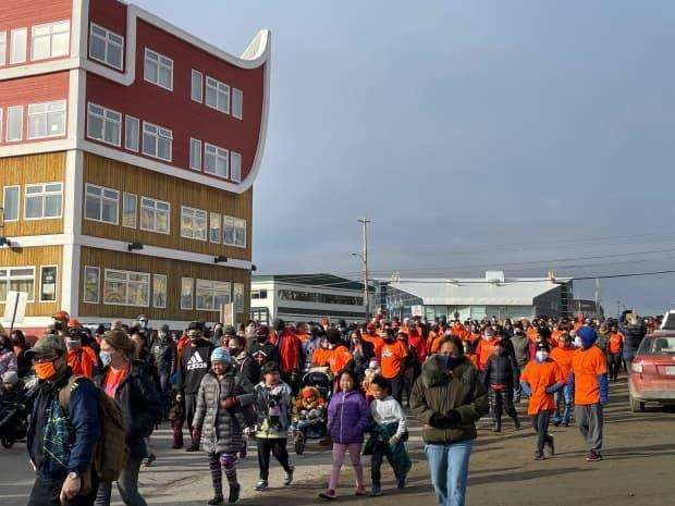 Hundreds of Iqaluit residents walk down Queen Elizabeth Way in Iqaluit on Thursday during theNational Day for Truth and Reconciliation. (Jane George/CBC - image credit)