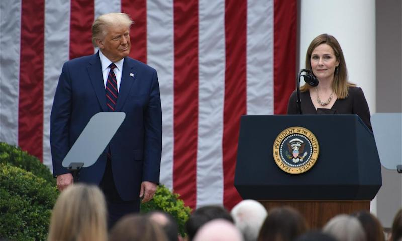 Donald Trump listens as Amy Coney Barrett speaks at the White House in Washington DC, on 26 September. Photograph: China News Service/Getty Images