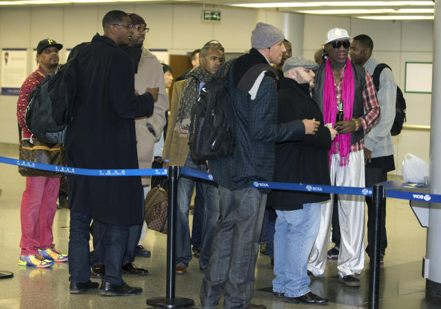 Former NBA basketball player Dennis Rodman, right, and former NBA players wait at the departure hall of Beijing International Capital Airport in Beijing Monday, Jan. 6, 2014. Rodman says he's going forward with an exhibition game including former NBA players in North Korea because he wants to connect with its people and let others know the sheltered communist country isn't so bad. (AP Photo/Andy Wong)