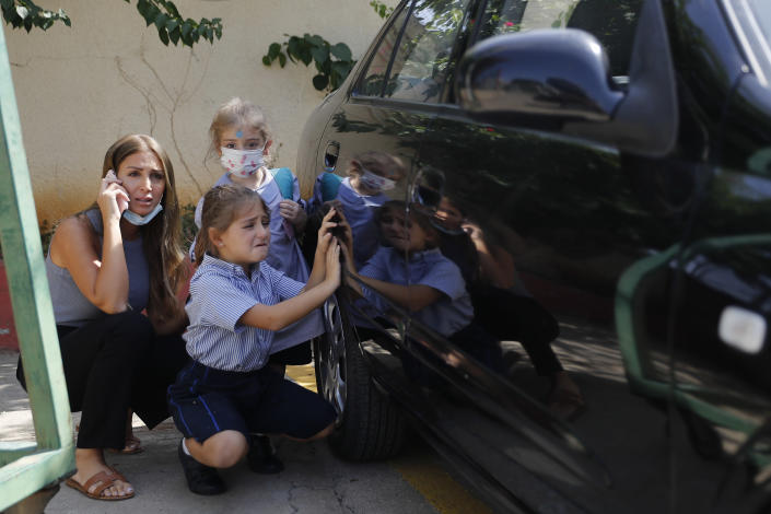 A Lebanese mother with her children hide behind a car from sniper fire outside a school, in the Christian neighborhood of Ain el-Remaneh, in Beirut, Lebanon, Thursday, Oct. 14, 2021. Armed clashes broke out in Beirut Thursday during the protest against the lead judge investigating last year's massive blast in the city's port, as tensions over the domestic probe boiled over. (AP Photo/Hussein Malla)