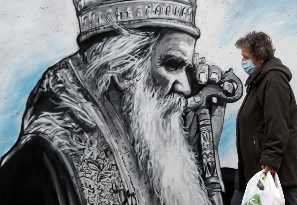 A woman wearing a mask against the spread of the coronavirus walks past graffiti depicting late Bishop Amfilohije in Belgrade, Serbia, Thursday, Nov. 26, 2020. After the two most senior Serbian Orthodox Church leaders died within a month after testing positive with the coronavirus, health experts and even hardcore believers are starting to worry. (AP Photo/Darko Vojinovic)