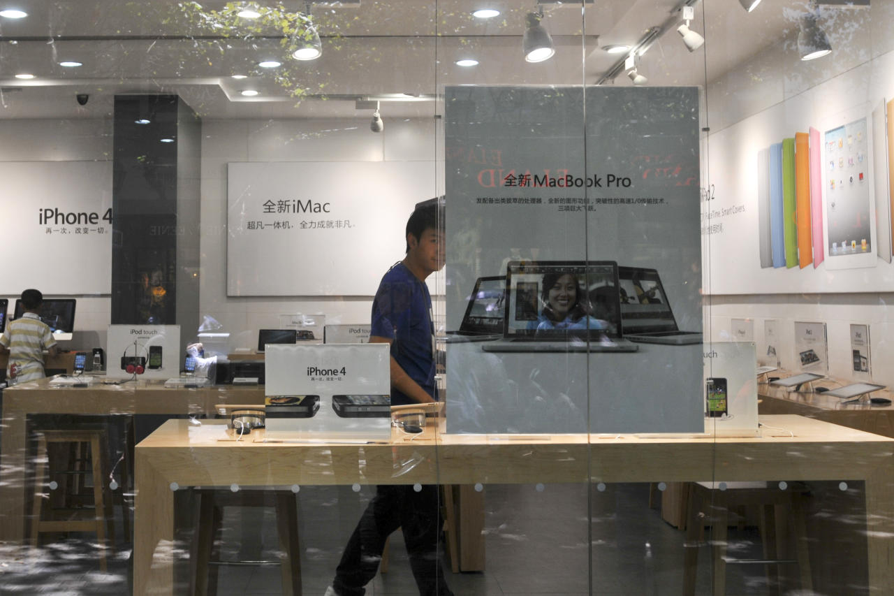A shopkeeper dressed as an Apple store employee looks out from a window of a shop masquerading as a bona fide Apple store in downtown Kunming, in southwest China's Yunnan province, Thursday, July 21, 2011. China, long known for producing counterfeit consumer gadgets, software and brand name clothing, has reached a new piracy milestone - fake Apple stores. (AP Photo) CHINA OUT