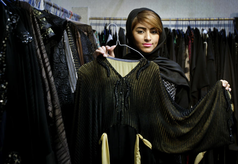 In this Saturday, April 13, 2013 photo, Emirati fashion designer Um Sultan of Marayer fashion presents an abaya designed by her during a bridal exhibition in Dubai, United Arab Emirates. Just a few years ago, Gulf Arab women usually only felt comfortable showing off their fashion sense at ladies-only parties or family gatherings. In public, at least in their home countries, the standard all-black abaya _ a simple floor-length covering and accompanying head scarf _ was the only culturally accepted option. But now a new generation of abaya designers are giving the traditional garment a twist with choices of fabric, designs and even some expensive bling to allow Gulf women a host of style options. (AP Photo/Kamran Jebreili)