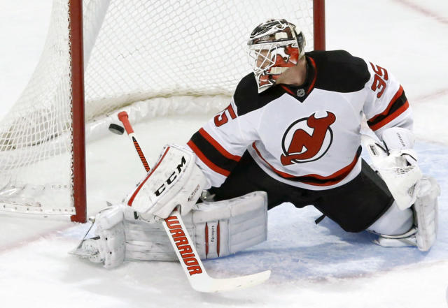 New Jersey Devils goalie Cory Schneider watches the goal of Chicago Blackhawks left wing Patrick Sharp slide behind him during the first period of an NHL hockey game Monday, Dec. 23, 2013, in Chicago. (AP Photo/Charles Rex Arbogast)