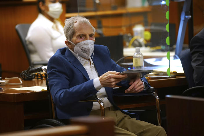 Robert Durst holds a device to read the real time spoken script as he appears in the courtroom of Judge Mark E. Windham as attorney's begin opening statements in the trial of the real estate scion charged with murder of longtime friend Susan Berman, in Los Angeles County Superior Court Tuesday, May 18, 2021, in Inglewood, Calif. Durst's murder trial was delayed more than a year due to the Covid-19 pandemic. (Al Seib/Los Angeles Times via AP, Pool)