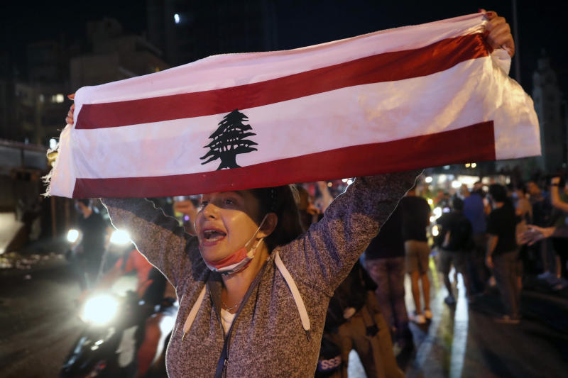 An anti-government protester chants slogans as she holds up a Lebanese flag joining others to block a road during a protest against the political leadership they blame for the economic and financial crisis, in Beirut, Lebanon, Thursday, June 11, 2020. (AP Photo / Hussein Malla)