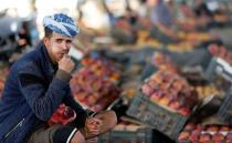 Fruit vendor chews qat, a mild stimulant, as he looks on at a fruit market amid concerns of the spread of the coronavirus disease (COVID-19) in Sanaa