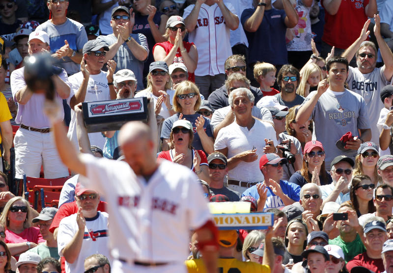 Boston Red Sox's Kevin Youkilis, foreground, tips his batting helmet as fans applaud in the second inning of a baseball game against the Atlanta Braves in Boston, Sunday, June 24, 2012. (AP Photo/Michael Dwyer)