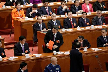 Chinese President Xi Jinping stand up with his ballot before a vote at the fifth plenary session of the National People's Congress (NPC) at the Great Hall of the People in Beijing, China March 17, 2018.  REUTERS/Jason Lee