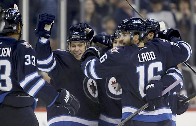 Winnipeg Jets' Dustin Byfuglien (33), Bryan Little (18), Grant Clitsome (24), Andrew Ladd (16) and Zach Bogosian (44) celebrate after Clitsome scored against the Washington Capitals during the second period of an NHL hockey game in Winnipeg, Manitoba, Tuesday, Oct. 22, 2013. (AP Photo/The Canadian Press, Trevor Hagan)