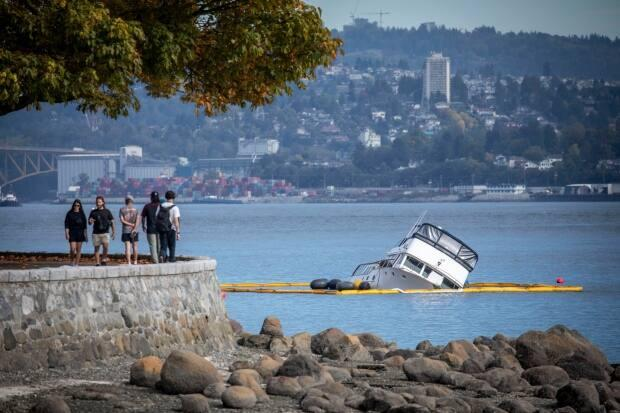 A crew works to prevent a capsized yacht from spilling fuel into the water in Vancouver's Coal Harbour on Monday, Sept. 21, 2021.  (Ben Nelms/CBC - image credit)
