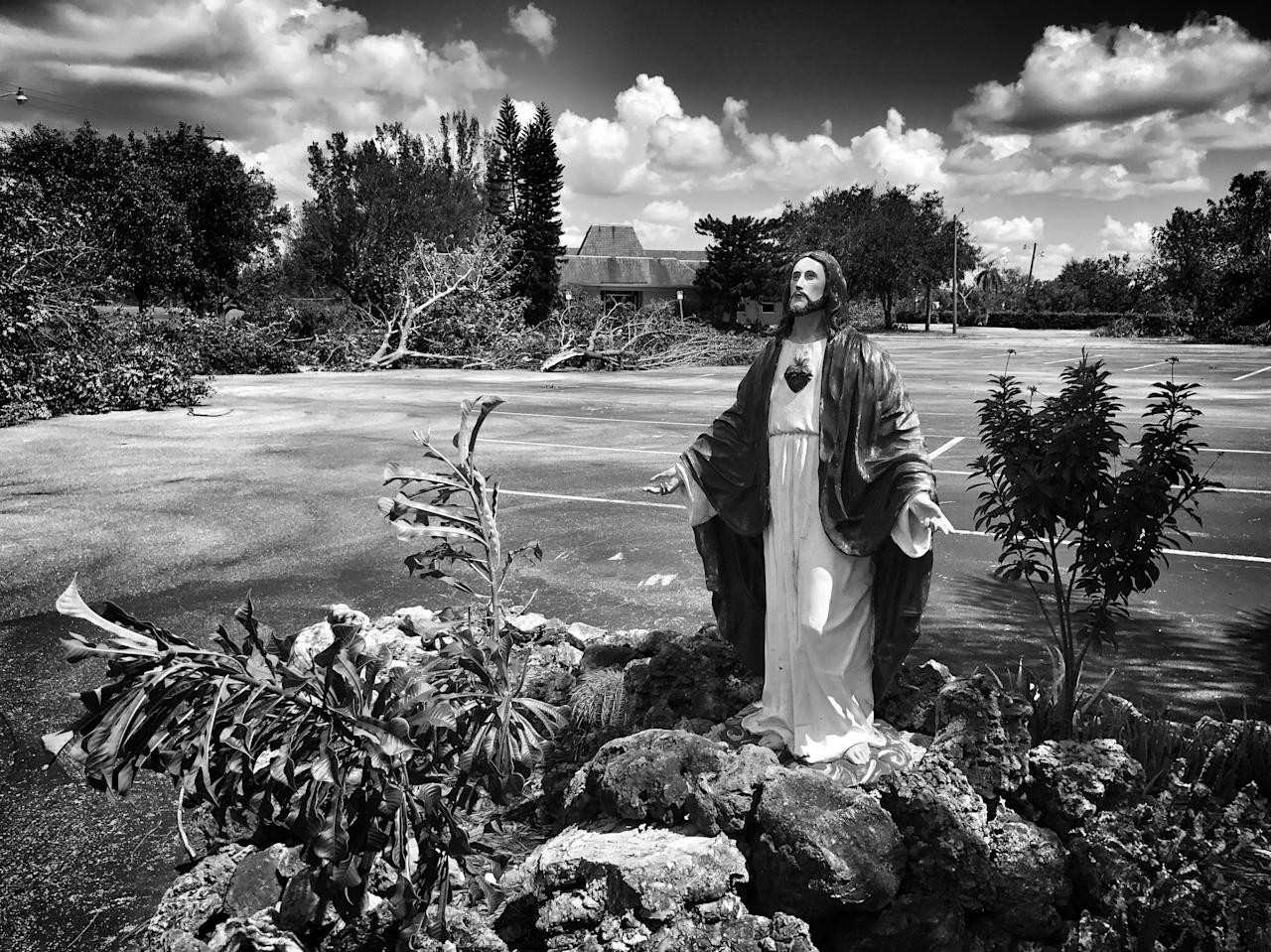 <p>A statue of Jesus stands amid storm debris from Hurricane Irma in Lehigh Acres, Fla. (Photo: Holly Bailey/Yahoo News) </p>