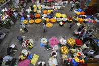 Flower vendors wait for buyers at a wholesale market in Bengaluru, India, Thursday, Sept. 24, 2020. The nation of 1.3 billion people is expected to become the COVID-19 pandemic's worst-hit country within weeks, surpassing the United States. (AP Photo/Aijaz Rahi)