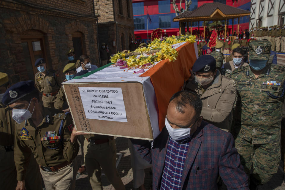 Indian police officers carry the coffin of their colleague Rameez Ahmad during a wreath laying ceremony in Srinagar, Indian controlled Kashmir, Thursday, April 1, 2021. Gunmen in disputed Kashmir on Thursday killed a policeman as they tried to storm the residence of a politician of India's ruling party, police said. (AP Photo/ Dar Yasin)