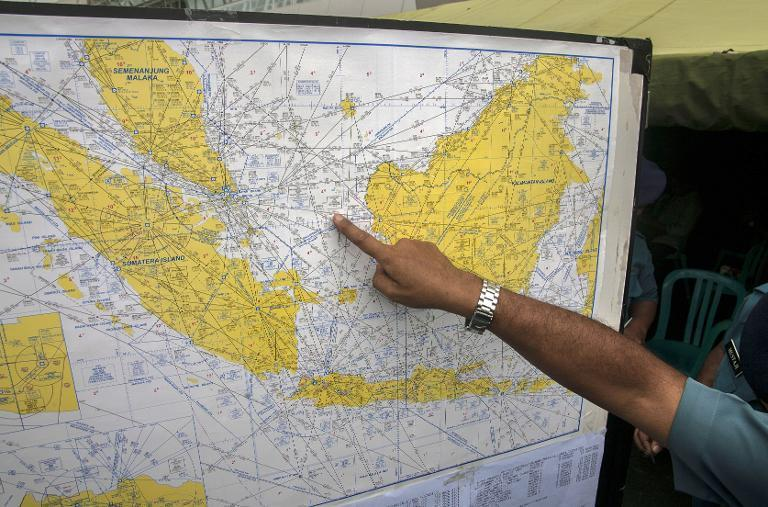 An Indonesian Air Force official points at the search area for the missing AirAsia flight QZ8501, at the airport in Surabaya, East Java, on December 29, 2014