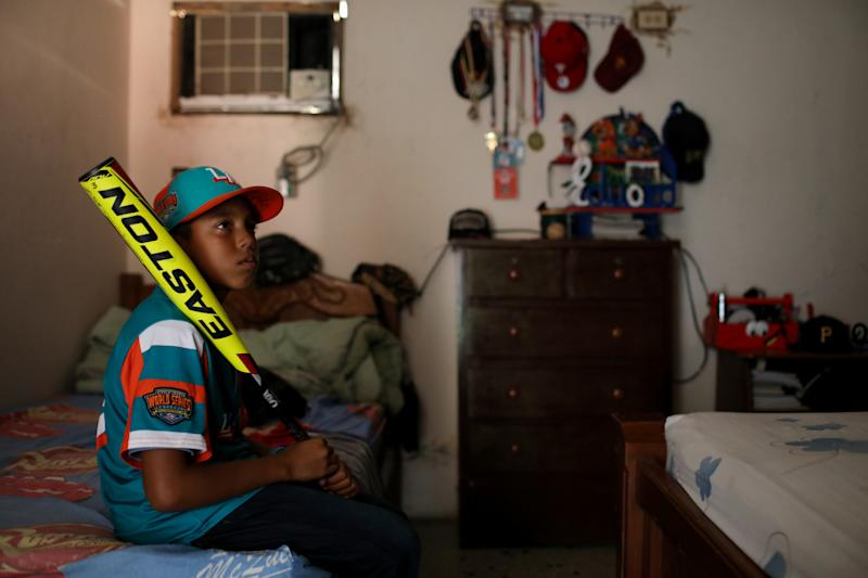 Baseball little league player Eduar Pinto, 12, poses for a photograph with a baseball bat, in his bedroom at his home in Maracaibo, Venezuela. (Photo: Manaure Quintero/Reuters)