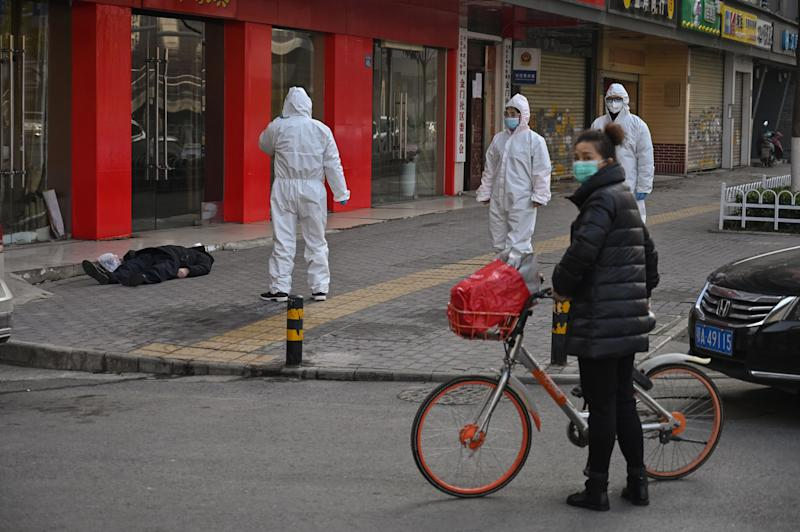EDITORS NOTE: Graphic content / This photo taken on January 30, 2020 shows officials in protective suits checking on an elderly man wearing a facemask who collapsed and died on a street near a hospital in Wuhan. - AFP journalists saw the body on January 30, not long before an emergency vehicle arrived carrying police and medical staff in full-body protective suits. The World Health Organization declared a global emergency over the new coronavirus, as China reported on January 31 the death toll had climbed to 213 with nearly 10,000 infections. (Photo by Hector RETAMAL / AFP) / TO GO WITH China-health-virus-death,SCENE by Leo RAMIREZ and Sebastien RICCI (Photo by HECTOR RETAMAL/AFP via Getty Images)